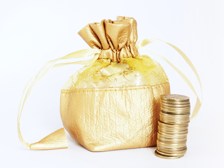 Golden money bag with a stack of golden Indian currency coins, isolated on white. Suitable for wealth building and money saving concepts photo