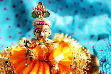 Brass idol of baby lord Krishna, a Hindu god, dressed in bright yellow clothing, against a polka dotted aqua colored cloth background, sporting his legendary musical flute. Ideal for Hindu religious use and festivals - like Janamashtami, Gokul ashtami. photo