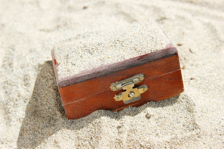 suspense: A closed wooden treasure trunk buried in a desert. Can be used for treasure, luck, suspense, and excavation concepts.