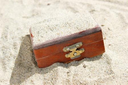 suspens: Un coffre en bois ferm� de tr�sor enfoui dans un d�sert. Peut �tre utilis� pour des concepts tr�sor, chance, suspense, et d'excavation. Banque d'images