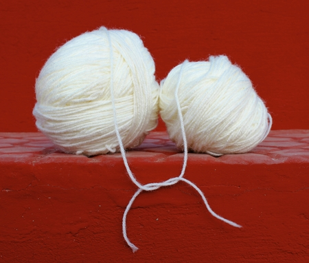 Two white wool yarn balls with their treads tied up in a knot, shot against a red concrete steps background. It can be used for relationship concepts like -love, togetherness, connection, and for business concepts like - mergers, joint venture etc. photo