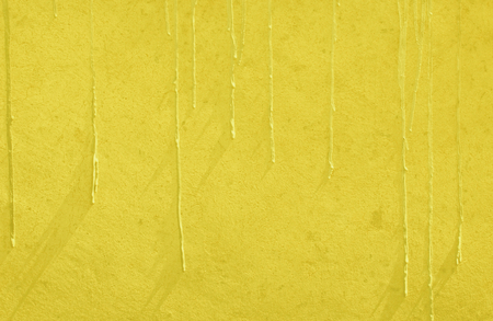 A yellow concrete plastered wall with paint drip texture. This vibrant colored wall will serve as a great background texture.