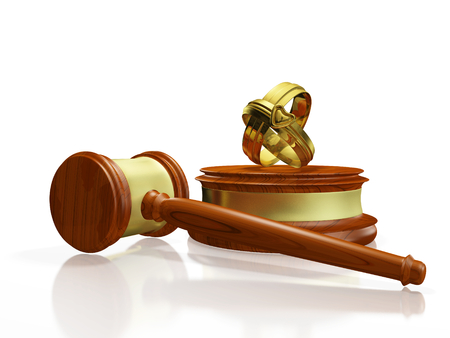 A 3D illustration of divorce with two gold wedding bands or rings placed on a judges wooden block with the gavel or mallet lying alongside. Ideal for use in divorce and matrimonial disputes related concepts. Stock Photo