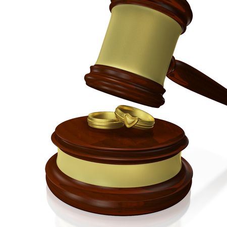 interlocked: A 3D illustration of a pair or interlocked gold wedding rings or bands, placed on a wood block with a wooden judges gavel or mallet about to hit them. Ideal for use in matrimonial disputes, legal separation and divorce related concepts. Stock Photo