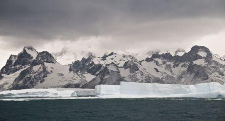 tabellare: Grande iceberg tabulare contro lo sfondo di una catena montuosa Sud georgiano.