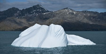 calved: A small iceberg floating far from the mountainous shores where it once calved from - South Georgia.