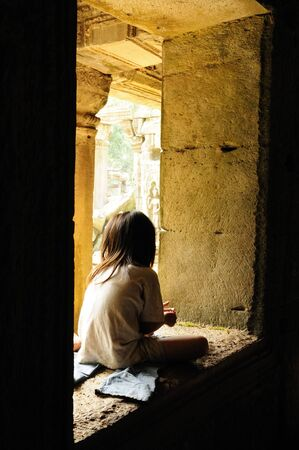 poor children: Homeless Girl Sitting in a Window at the Ancient Ruins of Angkor Watt Stock Photo