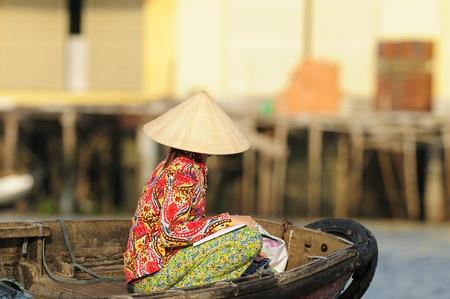 Een Vietnamese dame zitten op een boot op een ochtend markt in de Mekong Delta