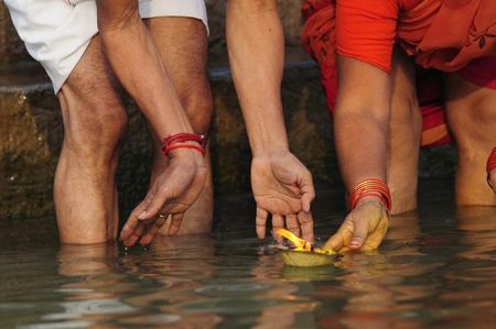 devout: Devout Hindus Floating an Offering of Flowers on the Ganges River.