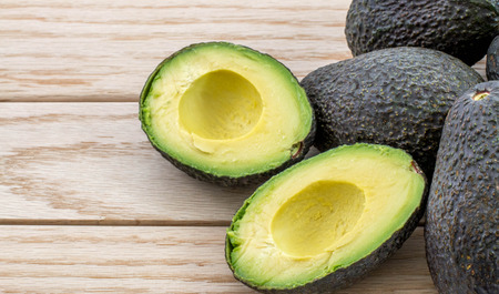 Avocados on a wood table and room for text