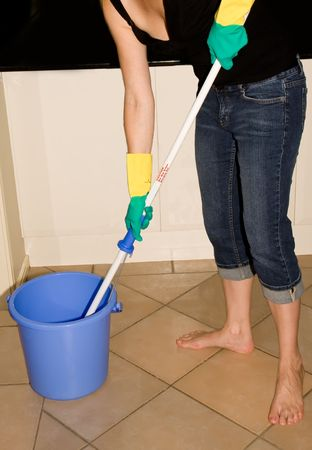 Woman cleaning tiled floor with a bucket of water and long-handled mop Stock Photo - 4888297