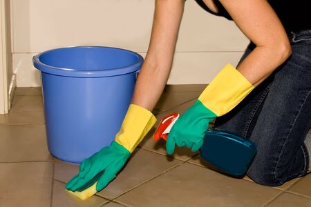 housewife gloves: Woman cleaning floor with sponge and spray detergent, whilst wearing rubber gloves Stock Photo