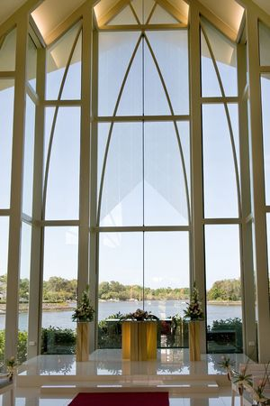 Modern wedding chapel with view through glass windows at lake photo