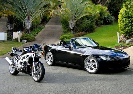 sportscar: Black sportscar and sportsbike pictured together against a tropical garden background