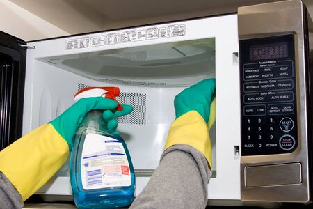 cleaned: Microwave being cleaned with a sponge and chemical spray, whilst wearing rubber gloves