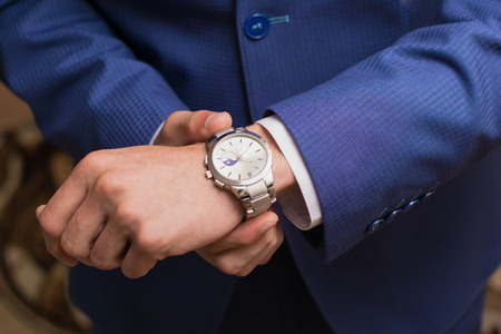 clock hand: Wedding photo. The groom puts on hours Stock Photo