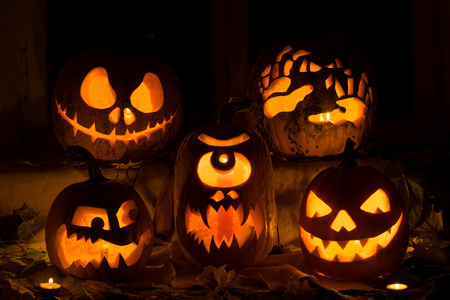 Photo composition from five pumpkins on Halloween. Jack, terrible hands, embittered, a Cyclops and evil pumpkin against an old window, leaves and candles.