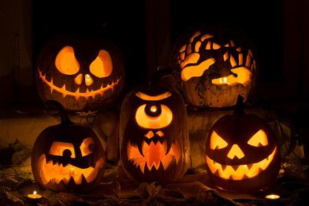 Foto Komposition aus fünf Kürbisse auf Halloween. Jack, schrecklichen Hände, verbittert, einem Zyklopen und böse Kürbis vor einem alten Fenster, Blätter und Kerzen. Standard-Bild