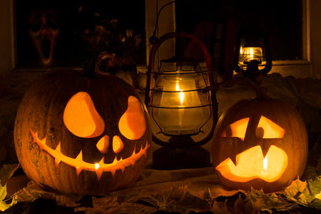 Photo composition from two pumpkins on Halloween. Jack and frightened pumpkins stand against dry leaves, candles and an old window in which the ghost looks