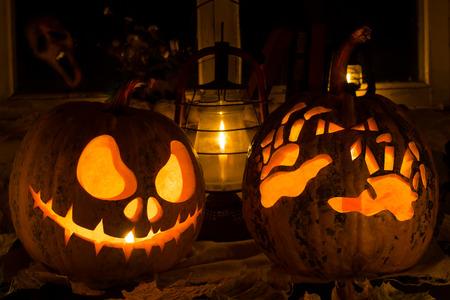 calabaza: Composición de la foto de dos calabazas en Halloween. Jack y las manos terribles contra una vieja ventana, hojas secas y un terrible fantasma en una ventana