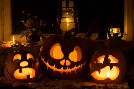 calabaza: Composición de la foto de tres calabazas en Halloween. Llanto, Jack y asustados calabazas contra una vieja ventana, hojas secas Foto de archivo