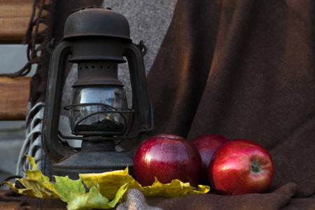 red oil lamp: Photo a still life an oil lamp and red apple against a brown drapery