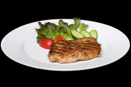 stake: Photo of a pork stake on a white plate with a cucumber, tomato and a lettuce leaf on a black background