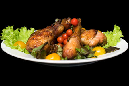 muslos: Photo of chicken thighs in honey sauce on a lettuce leaf on a black background