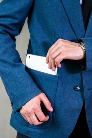 bussiness man: Young businessman in a white shirt hides a tablet in his jacket pocket Stock Photo