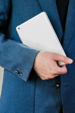 bussiness man: Young businessman in a jacket and white shirt, holding a tablet Stock Photo