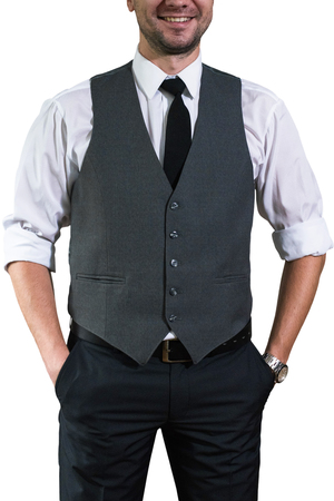 A young businessman in a white shirt with rolled up sleeves stands and keeps his hands in the pockets of his trousers. Hopster guy in a stylish gray waistcoat Stock Photo