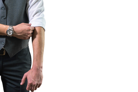 his shirt sleeves: A young businessman in a white shirt rolls up his sleeves preparing to work. A guy, a hipster in a gray waistcoat with a black tie. Ready for work Stock Photo