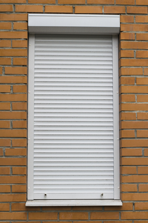rolling garage door: White metal protective roller shutters in white on a orange brick wall