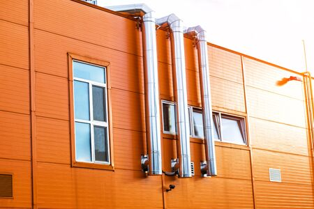 The facade of an industrial building. The building is orange with air conditioning, ventilation pipes and a metal staircase to the roof