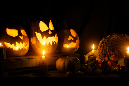 Photo for the holiday Halloween. Three evil pumpkins and a basket with different vegetables and candles