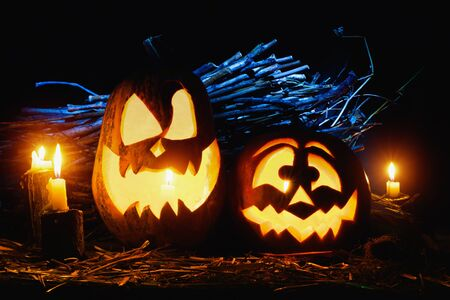 Photo for the holiday Halloween. Two evil pumpkins surrounded by candles on a dark background