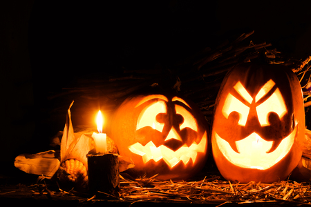 Photo for the holiday Halloween. Two evil pumpkins surrounded by candles and corn on a dark background. Image for postcard with copy space