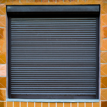 The texture of the window with blinds on the wall with ceramic tiles. Can be used as a background in interior design. Exterior of the facade of the house. Metal roller shutter for shop Banque d'images