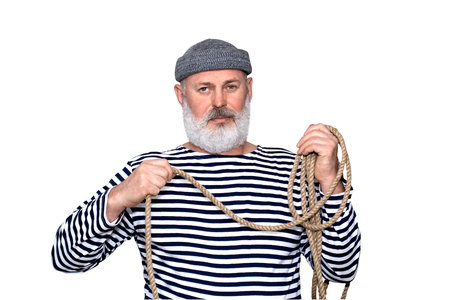 Portrait photo d'un marin joyeux tenant une corde. Un homme avec une barbe grise, vêtu d'une chemise à rayures noires et blanches et d'une casquette grise