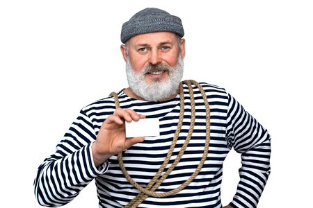 Photo sailor in a striped T-shirt. A middle-aged man with a gray beard is holding a white white business card. Photo to advertise your product.