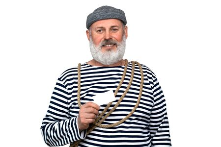 Photo sailor in a striped T-shirt. A middle aged man with a gray beard is holding a white business card. Photo to advertise your product.