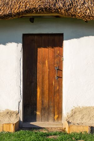 Traditional Ukrainian house. Wooden door to the house. Roof made of straw.