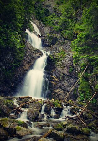 Very high amazing waterfall in a wooded mountainous landscape  photo