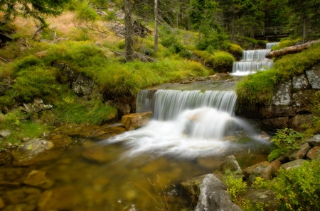 Amazing cascade in a wooded mountainous landscape  photo
