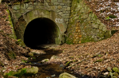 Tunnel wiht stream in witner forest landscape photo