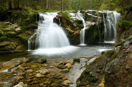 Amazing waterfalls in a wooded mountainous landscape  photo