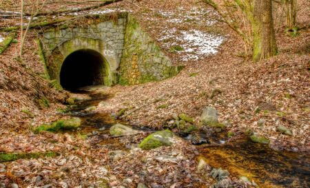 Tunnel with stream in winter forest landscape photo