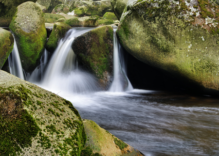 Nice peaceful cascade between mossy rocks and stones photo