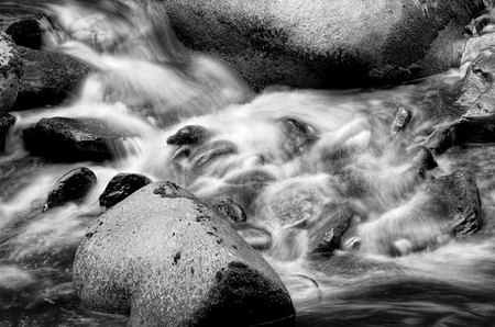 Black and white detail of small waterfall with ice and snow. photo