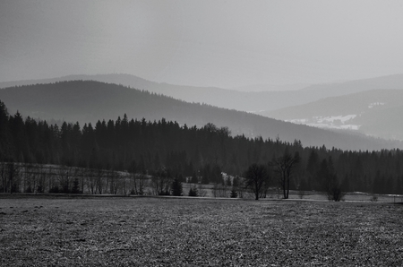 Black and white landscape of hills, mountains and valley in\ the fog